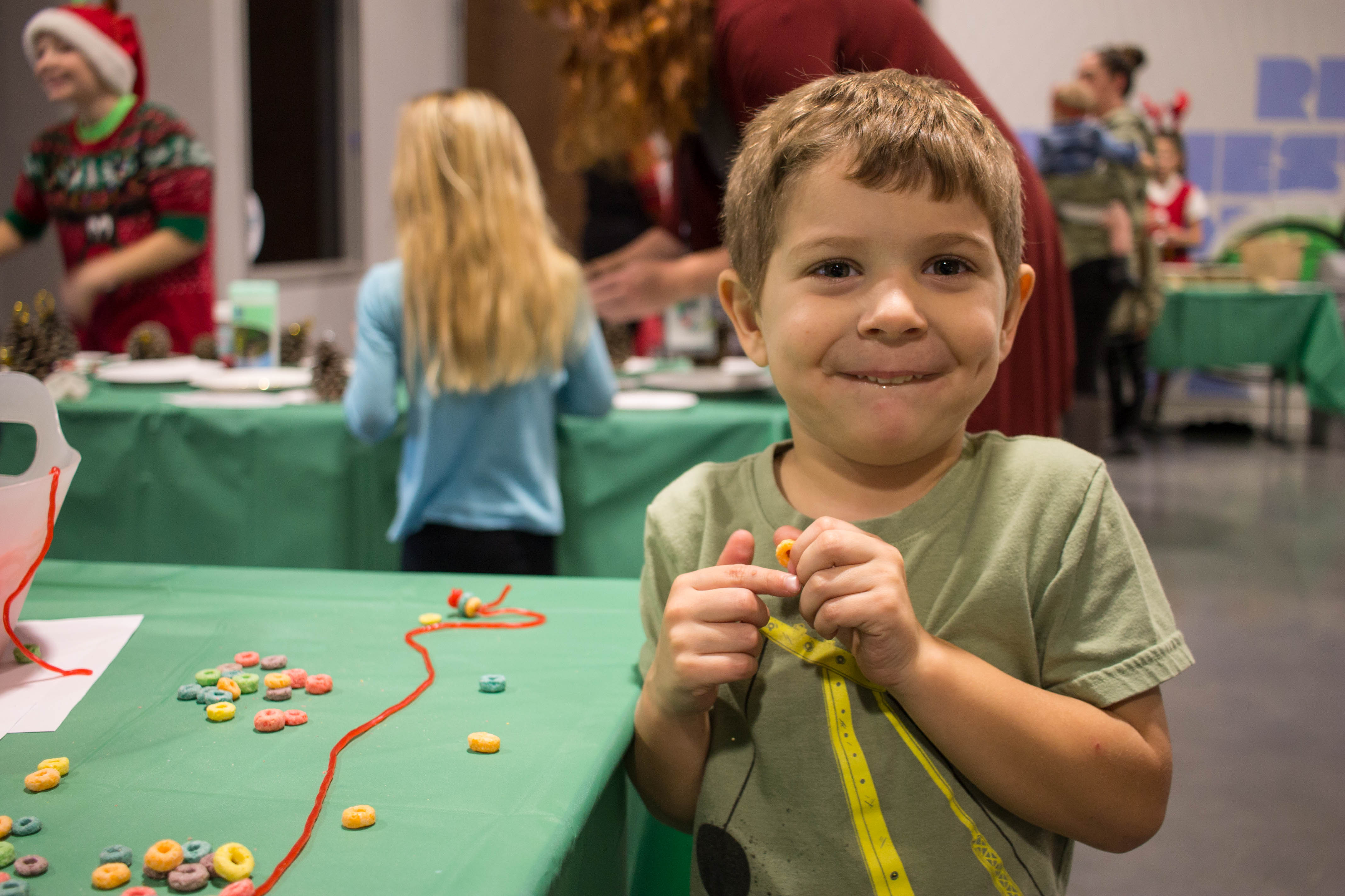 Johnny making a cereal necklace at the craft table during breakfast with Santa
