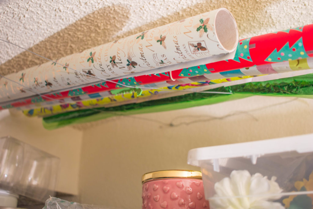 wrapping paper storage hack: on the ceiling of the closet