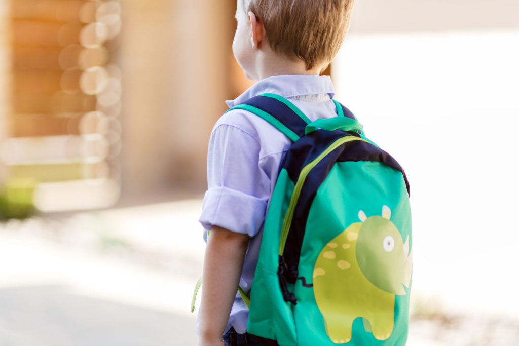 boy wityh backpack walking to first day of kindergarten
